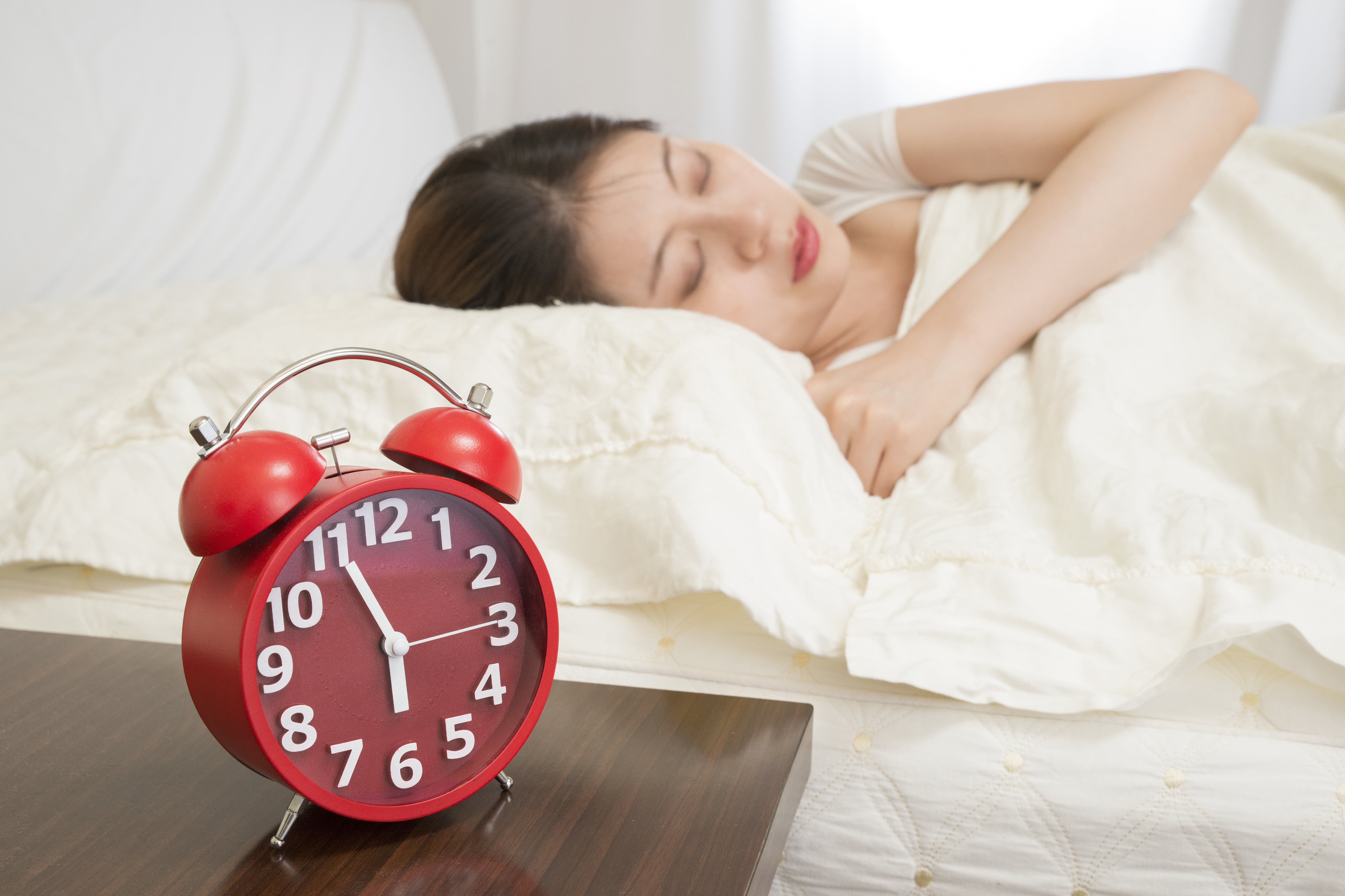 young lady sleeping in bed with a red alarm clock