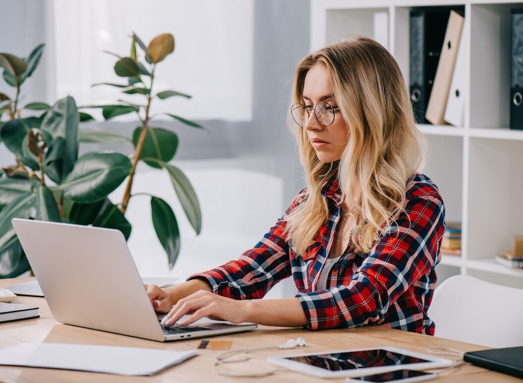 Young lady with glasses and flannel shirt using a laptop